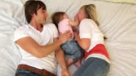 Family with young child playing together on bed video