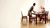 Family's having breakfast in the dining room: mother serves omelet to her son and husband video
