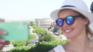 Famous Roman landmark - Coliseum. Tourist woman making selfie video