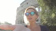Famous Roman landmark - Coliseum. Tourist woman sending kisses video