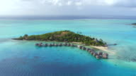 AERIAL: Fantastic hotel resort with luxury overwater bungalow villas above the ocean on small private island with stunning secluded white sandy beaches facing exotic ocean reef video