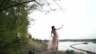 Fantasy girl slowly dancing with her veil on the wind at lakeshore. Magical moves of innocent nymph of the wilds video