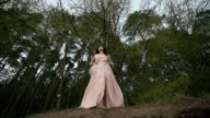Fantasy girl slowly dancing with her veil on the wind in evening forest. Magical moves of innocent nymph of the wilds video