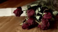 Farewell letter with faded rose bouquet on wooden table video