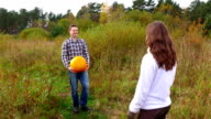 Farmer bring big heavy pumpkin and give his wife, woman take it with difficulty video