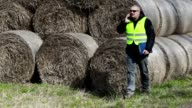 Farmer checking hay bales and talking on smartphone video
