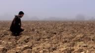 Farmer checks on poor soil. Long shot video
