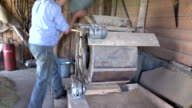 Farmer draw grain with bucket and pour into sifting machine video