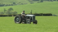 Farmer driving old vintage tractor in farm field (Agriculture) video