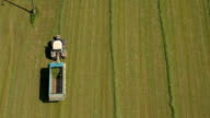 AERIAL: Farmer in tractor working on farm field and collecting fodder in wagon video