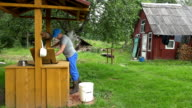 Farmer man at well house draw water and pour into bucket. video