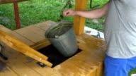 Farmer man open well house door and sink bucket on chain inside video