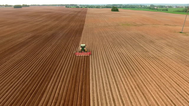 Farmer seeding, sowing crops at field.Aerial view video