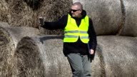 Farmer take pictures on tablet PC near the hay bales video