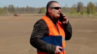 Farmer talking on smart phone at the field where the tractor harrow the ground video
