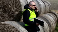 Farmer talking on smartphone near the hay bales video