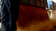 Farmer unloading wheat in a silo, slow motion video
