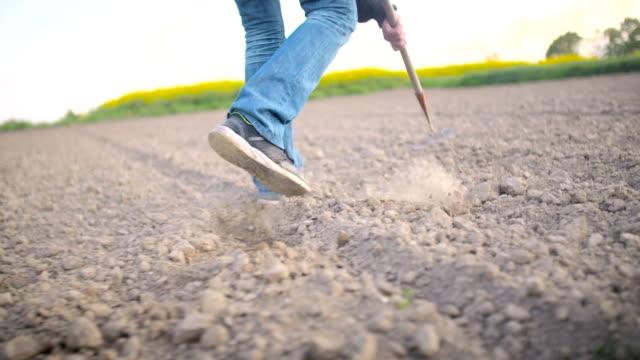 Farmer Using Hoe On Dirt At Farm video