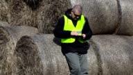 Farmer using tablet PC near the hay bales video