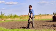 farmer weary boy digs ground old dirty shovel on dry ground video slow motion video