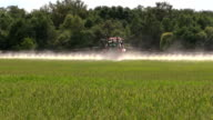 Farmer with tractor spray summer green wheat crop farm field video