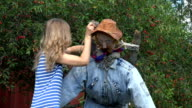 farmer woman stand scarecrow on cherry tree to protect berries. 4K video