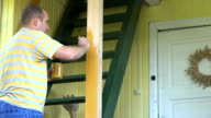 Farmer worker man hold jar with paint and painting wooden column with brush in yellow color. video