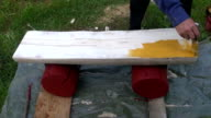 Farmer worker painting handmade  wooden bench with yellow paint video