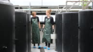 Farmers walking amidst storage tanks in fish farm video