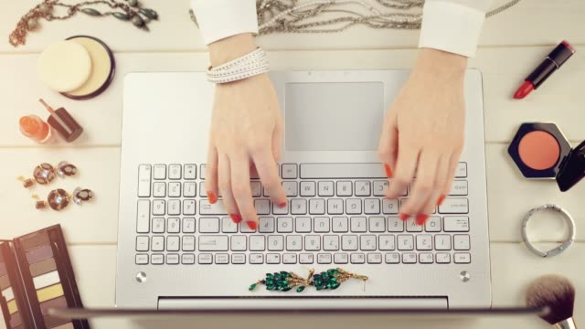 fashion blogger concept - woman with red polished nails working on laptop video