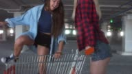 CU fashion funny young hipster teen girls having fun at the shopping mall parking, riding in shopping cart. 60 FPS video