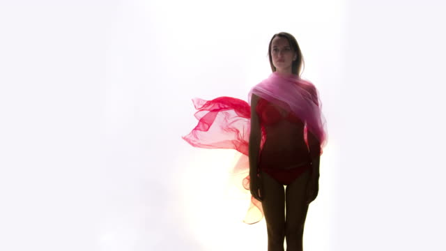 Fashion model in bikini with flowing red fabric video