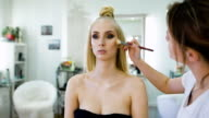 fashion stylist, creating an image for the top model. She was prepared for a photo shoot or fashion show on the catwalk. Expressive makeup video
