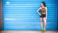 Fashion woman with roller skates posing over blue background video