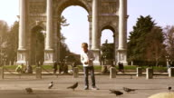 Fashionable boy feeds doves in Parco Sempione in Milan video