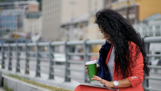 Fashionable curly lady drinks coffee and work on tablet at urban road background video