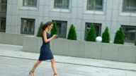 Fashionable woman using tablet pc walking outside. Modern businesswoman wearing stylish clothes and glasses video