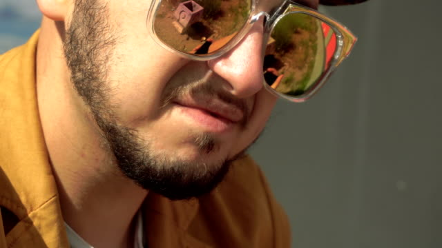 fashionable young man in golden sunglasses outdoors video