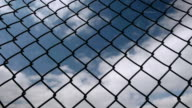Fast moving clouds behind a chain link fence. video