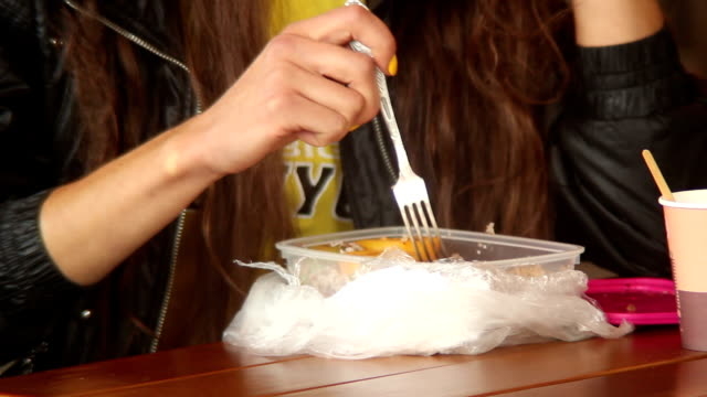 Fast-food eating with fork, drinking coffee, young adult woman video