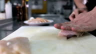 Fat and sinews being cut away from chicken breasts video