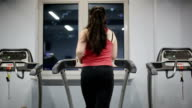 Fat female teenager on treadmill in gym video