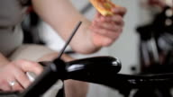 Fat man eating pizza, spinning exercise bike pedals video