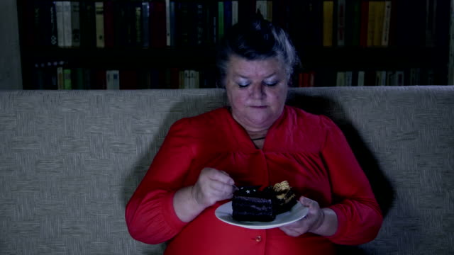 Fat senior woman watching tv show and eating cake video