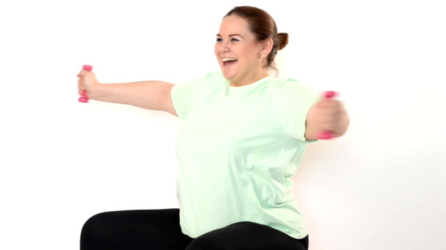 Fat woman making exercises with dumbbells video