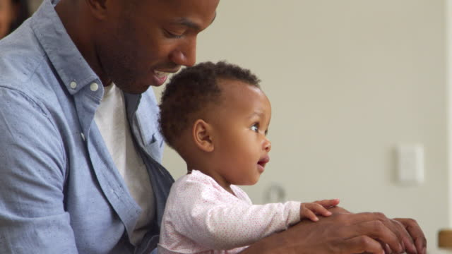 Father And Baby Daughter Using Laptop At Home Together video