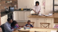 Father And CChildren Drawing At Table As Mother Prepares Meal video