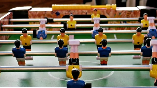 Father and child play kicker table football soccer video