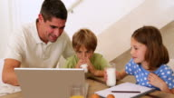 Father and children using laptop together at the breakfast table video