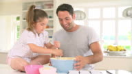 Father And Daughter Baking Cake In Kitchen video